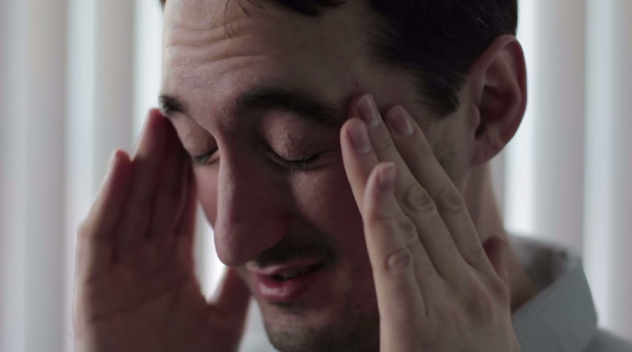 A man rubbing his temples with his eyes closed and a look of pain on his face