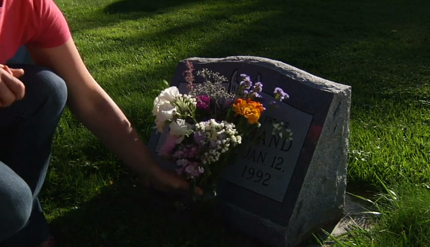 a woman putting flowers on a grave