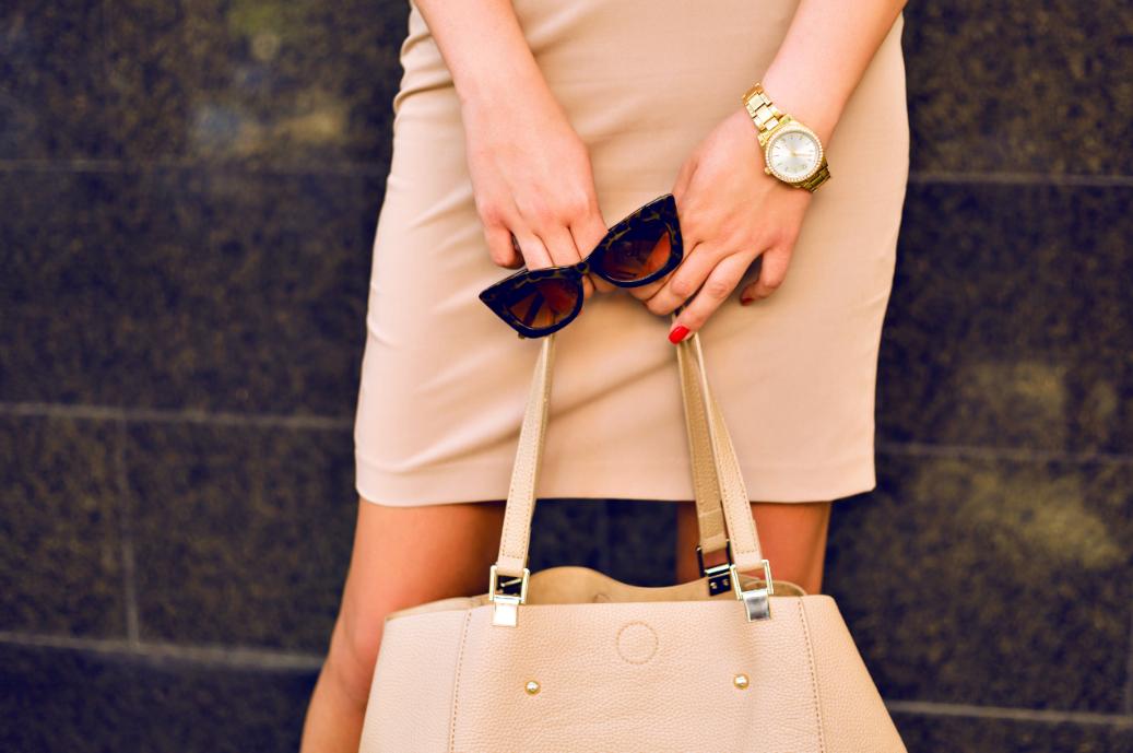 Woman holding handbag and sunglasses over her skirt