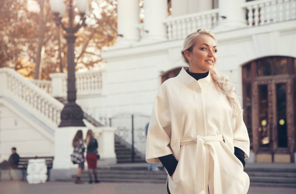 Attractive young woman wearing a white coat and taking a walk outside